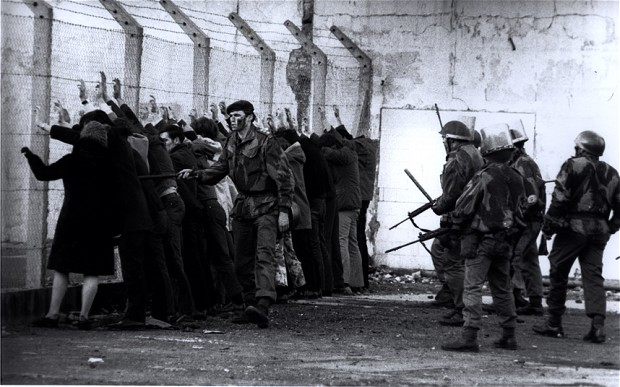 Demonstrators are rounded up by soldiers and lined up against a wall